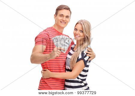 Joyful young man holding bunch of money and posing with his girlfriend isolated on white background