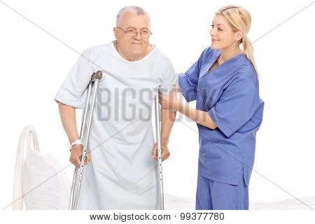 Young female nurse helping a senior patient with crutches isolated on white background