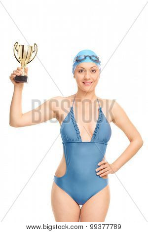 Vertical shot of a female swimming champion holding a gold cup and looking at the camera isolated on white background
