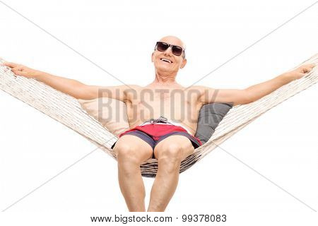 Relaxed senior man in red swim trunks lying on a hammock isolated on white background