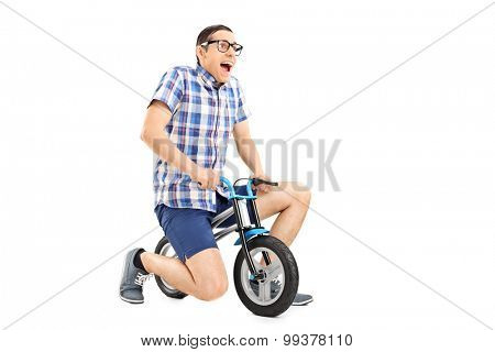 Studio shot of a silly young guy riding a tiny bicycle isolated on white background