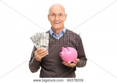 Joyful senior holding a few stacks of money in one hand and a piggybank in the other isolated on white background