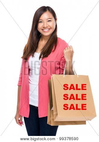 Happy woman with shopping bag and showing three sale word