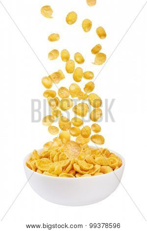 Corn flakes falling in bowl isolated on white background