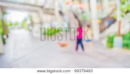 Blur Image Of People At Long  Corridor With Open Space To The Green Garden