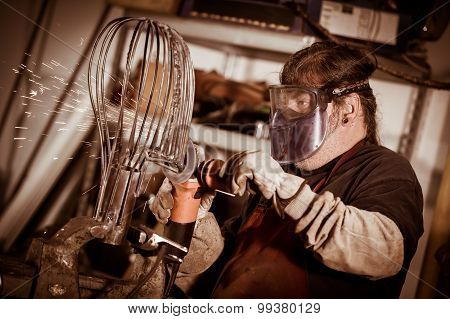 Metal Worker Grinding With Sparks In Workshop