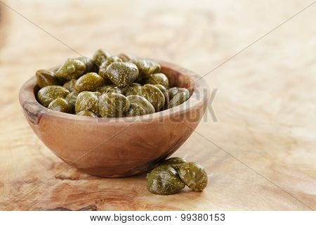 marinated capers in bowl on olive board