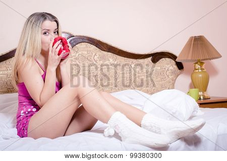 Beautiful happy blond young woman drinking hot tea