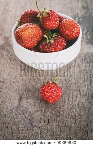 fresh strawberries in bowl on wood table