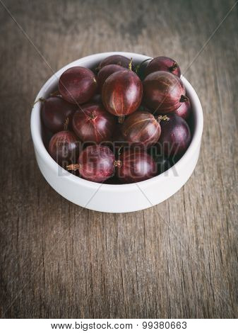gooseberries in a bowl on a wood background