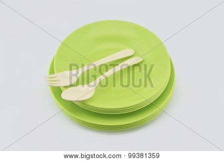 Stack Of Green Plastic Plate And Dish With Spoon Isolated On White