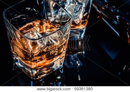 Close-up Of Top Of View Of Glass Of Whiskey Near Bottle On Black Table With Reflection, Old Style
