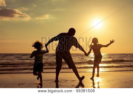 Father And Children Playing On The Beach At The Sunset Time.