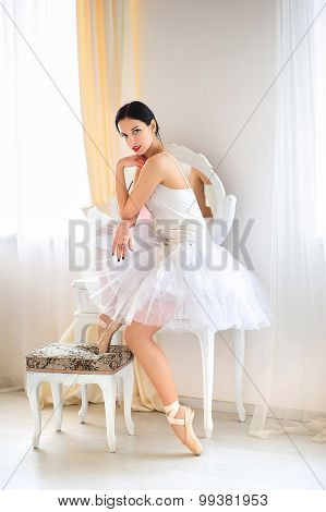 Brunette ballerina in room, wearing  costume, ballet skirt and corset