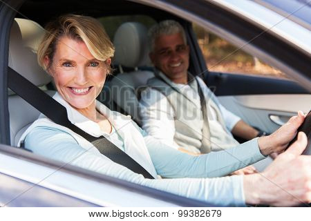 happy senior couple travelling in a car