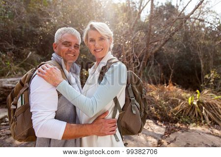 portrait of happy middle aged couple hugging in forest