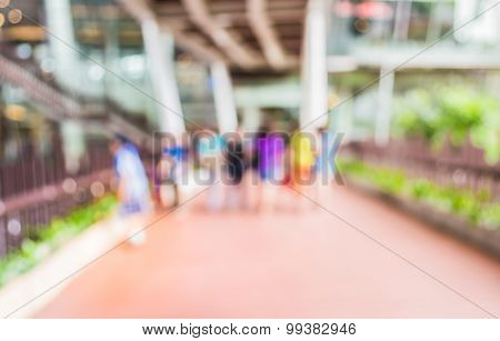 Blur Image Of People Walking At Corridor With Open Space To The Green Garden
