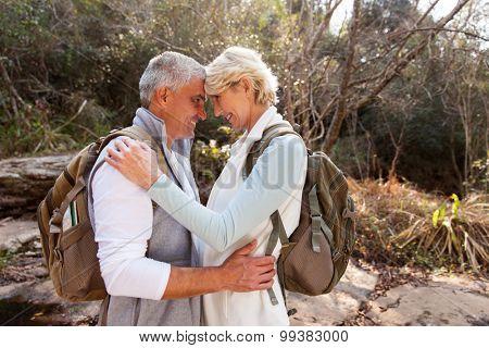 romantic senior couple hugging in forest