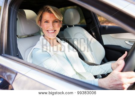 happy middle aged woman driving a car
