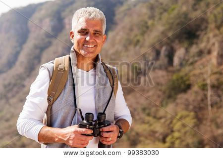 happy mid age man on top of the mountain with binoculars