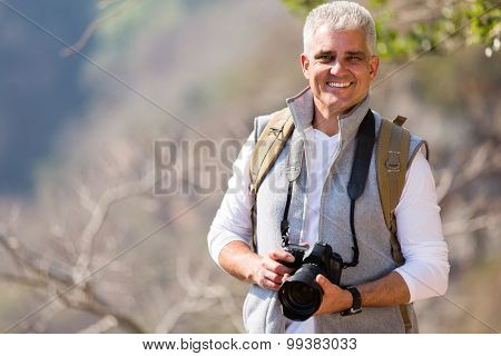 handsome mid age photographer standing in mountain valley
