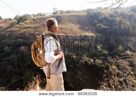 rear view of senior man with backpack standing on top of the mountain