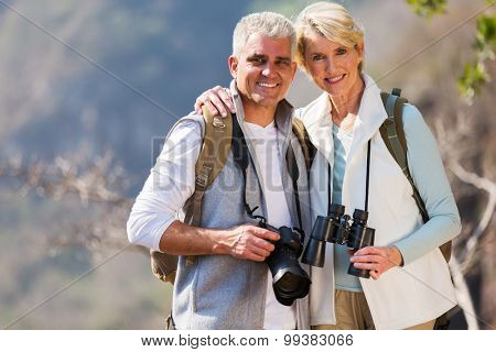 portrait of middle aged couple hugging in mountain