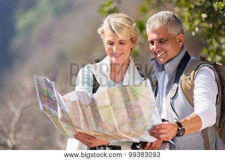 happy senior hikers looking at map
