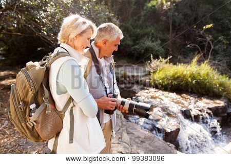 happy mid age hikers looking at river