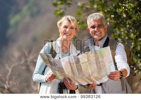 cheerful mid age couple hikers holding a map