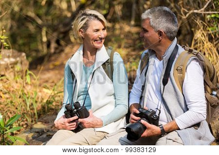 cheerful middle aged couple resting in mountain valley