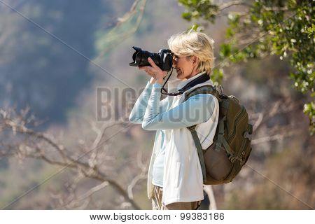 happy senior hiker taking photos with digital camera