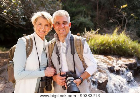 portrait of cute mid age couple standing in mountain valley