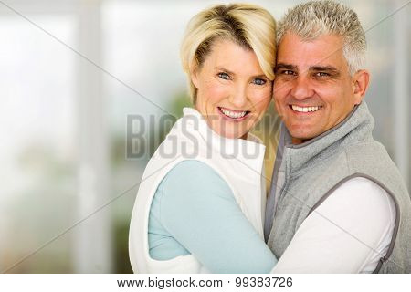 beautiful middle aged couple embracing at home