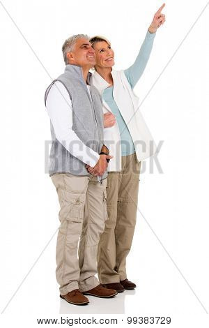 lovely senior couple pointing at empty copy space