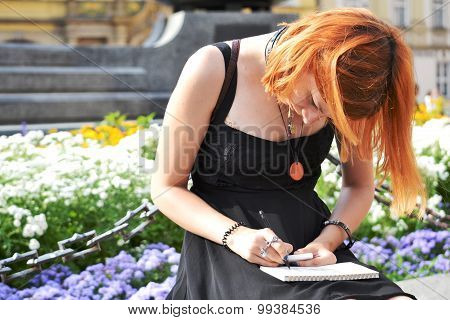 Red-haired girl of 17 in a light sundress black dress, a pencil drawing in an album. The Old Town Sq