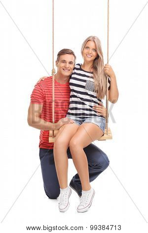 Vertical shot of a blond woman sitting on a wooden swing and posing with her boyfriend isolated on white background