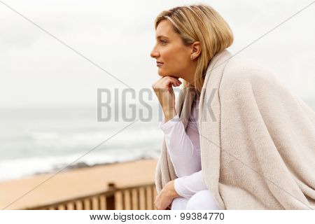 thoughtful woman with hand on chin looking away