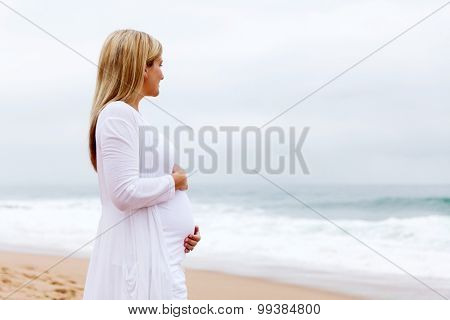 peaceful pregnant woman posing at the beach