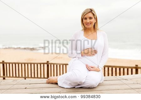attractive pregnant woman sitting at the beach