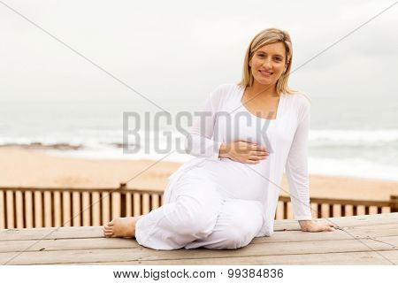 portrait of pretty pregnant woman touching her tummy