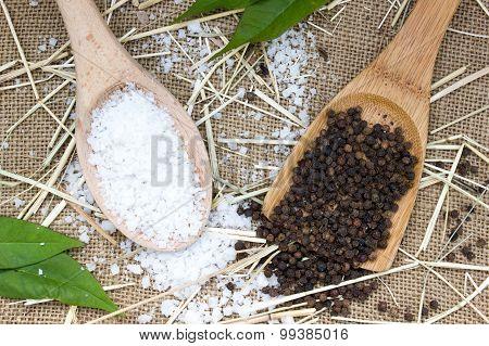 Sea Salt And Black Pepper In Wooden Spoon On Burlap Sack Background