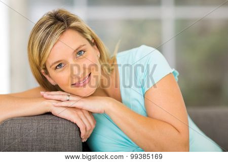 pregnant woman lying on a couch looking happy