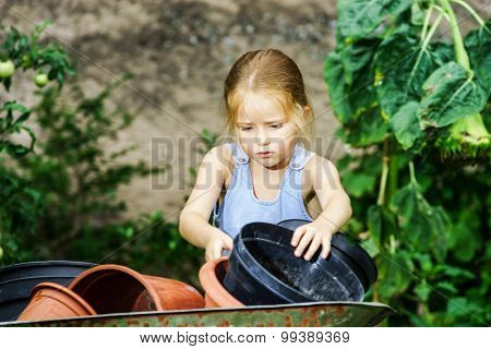 Cute Little Girl Helping Her Mother In The Backyard