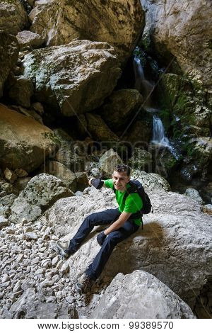 Happy Teenager Hiking Near A Waterfall In A Cave