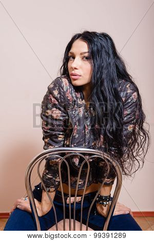 Young coquette female with beautiful long hair sitting on retro chair
