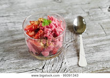 Frozen Yogurt With Strawberries And Cookie Crumbs In A Glass Bowl On A Light Wooden Background