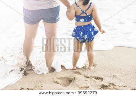 Woman and girl playing on the beach