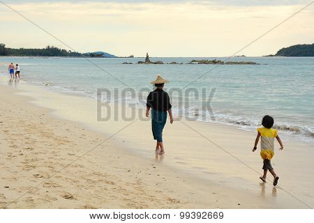 Burmese People Walking On The Beach