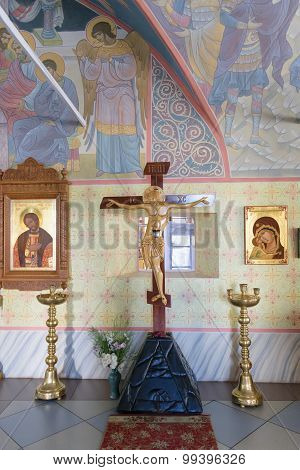 Crucifixion Of Jesus Surrounded By Icons In Church With Hand-painted Walls And Ceilings